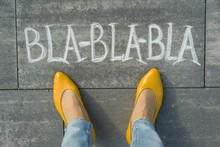 Female Feet With Text Bla-bla-bla Written On Grey Sidewalk