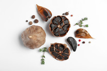 Aged Black Garlic With Thyme And Peppercorns On White Background, View From Above