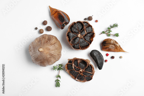 Fotografía  Aged black garlic with thyme and peppercorns on white background, view from abov
