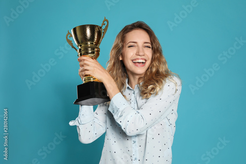 Fotografering  Portrait of happy young woman with gold trophy cup on blue background