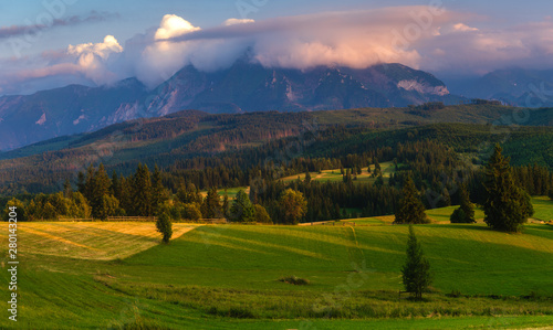 Wall Murals Melon Tatra Mountains. Mountain peaks towering over green grassy hills. Above the peaks, beautiful storm clouds illuminated by the setting sun