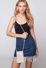Three Quarter Shot Of Blonde Girl, Wearing Black Vest Top And Short Denim Skirt With The Fringe. She Has Crossbody Phone Pearls Bag On A Shoulder. Girl Is Posing On Grey Background