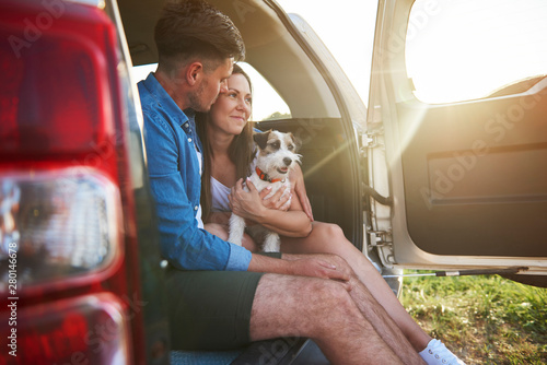 Loving couple with dog enjoying the view in summertime - 280146678