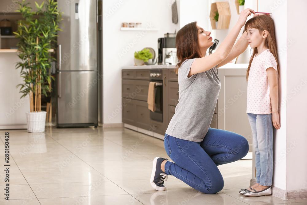 Fototapety, obrazy: Mother measuring height of little girl near wall