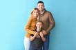 Leinwandbild Motiv Happy couple with little adopted boy on color background