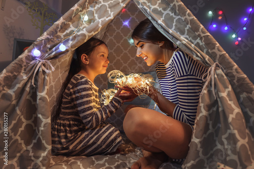 Fototapeta  Mother and her little daughter with fairy lights in evening at home