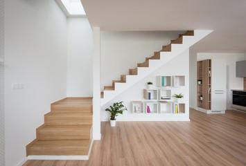 Wnętrze współczesnego salonu z drewnianymi schodami