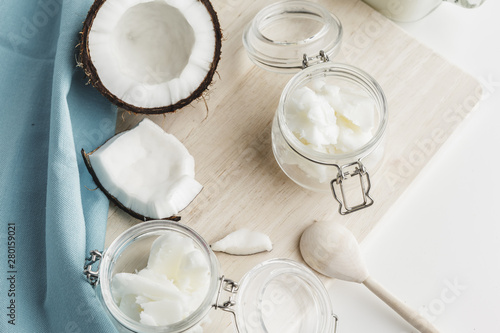 Organic healthy coconut butter and fresh coconut pieces on wooden board