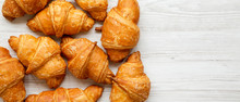 Freshly Baked Golden Croissants On A White Wooden Background, Top View. Space For Text.