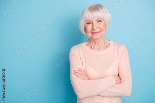 Portrait of charming lady with crossed hands looking peacefully at camera wearing pastel jumper isolated over blue background