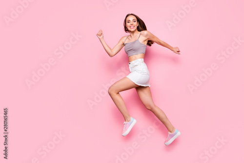 Full length profile side photo of pretty lovely millennial running smiling isolated over pink background