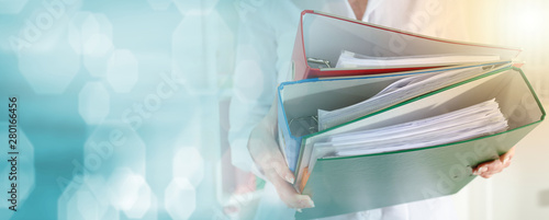 Photographie Businesswoman holding binders; light effect
