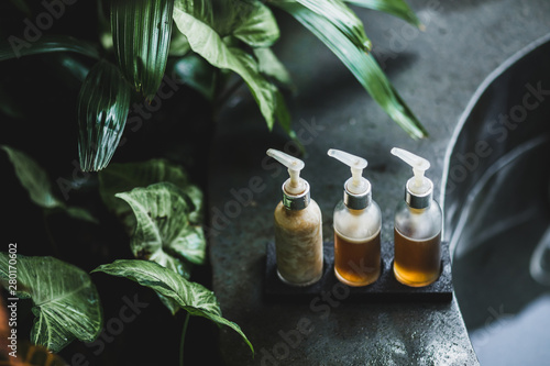 Obraz Different bottles for spa treatment on the edge of stone bath with tropical nature background. Wellness concept. - fototapety do salonu