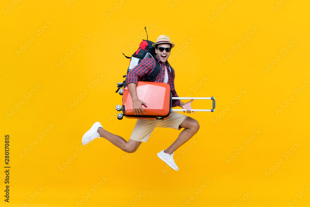 Fototapeta Excited happy young Asian man tourist with luggage jumping