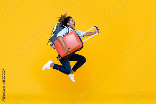 Foto  Excited African American woman tourist woman with backpack and luggage jumping