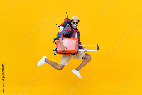 Fotografia  Excited happy young Asian man tourist with luggage jumping