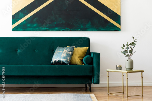 Cuadros en Lienzo Luxury and minimalistic composition of home interior design with stylish velvet sofa, pillows, gold coffee table, flowers in vase and elegant accessories