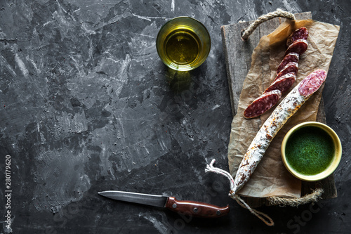 Valokuva  Sausage on a dark background with elements of cooking