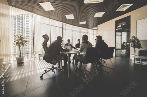 A team of young businessmen working and communicating together in an office. Corporate businessteam and manager in a meeting - fototapety na wymiar