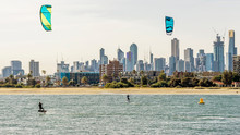 Pair Of Kitesurfers Trains In Port Phillip Bay, With The Skyline Of Melbourne, Australia In The Background