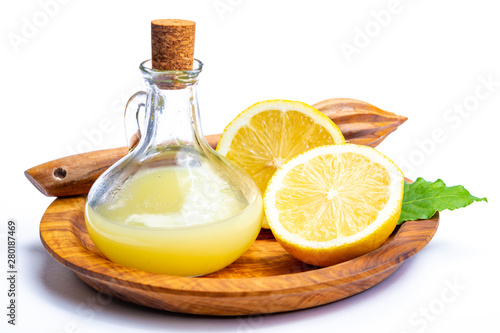 Fresh lemon juice made from ripe yellow Sicilian lemons used for cooking in glass bottle on olive wood plate