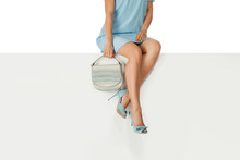 Beautiful Legs Woman Wearing Blue Dress With Blue Purse Hand Bag, High Heels Shoes Sitting On White Bench. Copyspace.