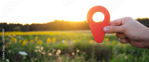 A hand is holding a red location marker in the sunset background. The concept of tourism and travel. Navigation and exploration. Destination. Holiday, vacation. Buying building land. Selective focus - fototapety na wymiar