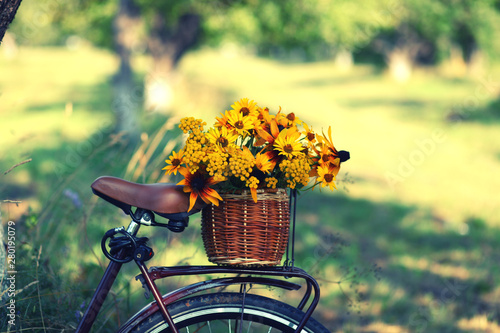 Türaufkleber Fahrrad a bicycle with a bouquet of yellow flowers in a basket against nature background