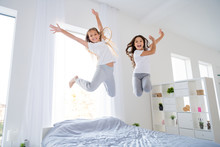 Low Angle Photo Of Cheerful Kids Jumping Bed Have Free Time Raise Hands Feel Content Room Indoors Apartment