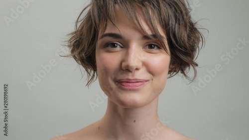 Fotografie, Obraz  Shy young woman with natural skin smiling while looking at the camera over grey