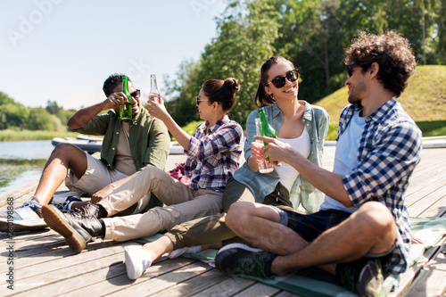 leisure, picnic and people concept - friends drinking beer and cider on lake pier in summer park