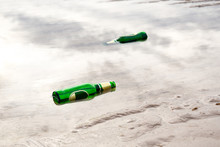 Envelopment Concept, Empty Green Beer Bottle On The Beach.