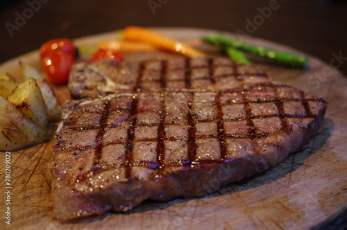 Recess Fitting Steakhouse Grilled T bone steak with potato, carrot, cherry tomato and asparagus on wood plate
