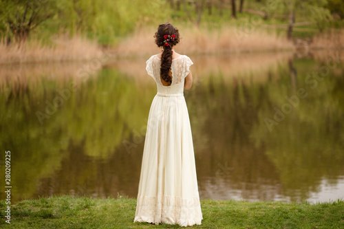 Rear view of a young anonymous bride in a beautiful full wedding dress, with hairstyle, looking down, nature background.