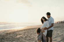 Family Vacation On The Beach. Father, Pregnant Mother, And Daughter Standing On The Beach Enjoying The Sunrise