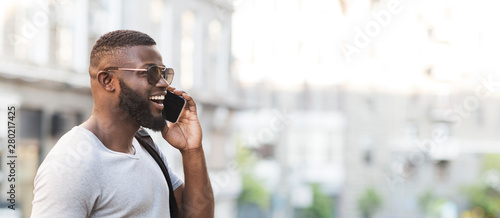 Fotografía  Smiling african man talking on cellphone with close friend