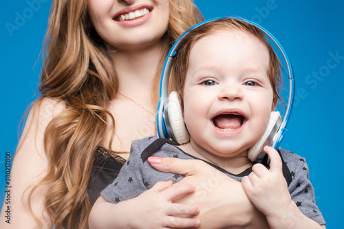 Studio portrait of cute little boy listening to music in headphones sitting on his mother s arms. Isolate on blue. - 280217808