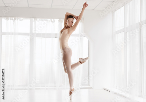 Fototapeta  Young Lady Dancing Classic And Modern Ballet In Spacious Studio
