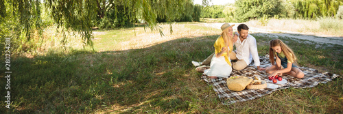 Family picnicking outdoors with daughter, resting in park