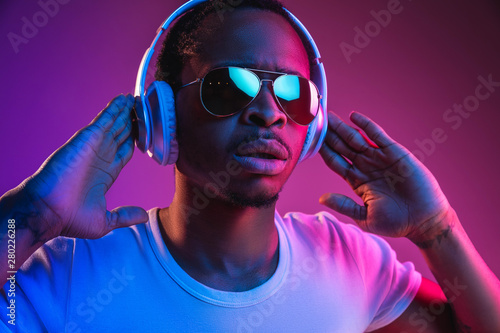 Fototapeta Young african-american man's listening to music in headphones in neon light on gradient background
