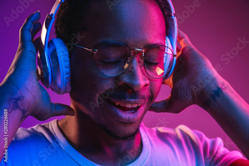 Leinwand Poster  Young african-american man's listening to music in headphones in neon light on gradient background