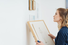 Young Woman Contemplating Where To Hang A Picture