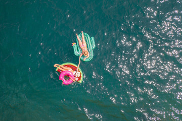 Drone point of view of two young women floating on inflatable mattresses above beautiful lake; girls relaxing on inflatable watermelon and cactus enjoying vacations