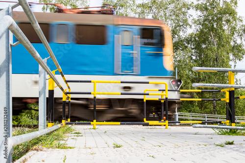 Valokuva InterCity train engine passing level crossing for pedestrians