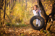 Little Girl Swinging On A Rubber Wheel From A Car