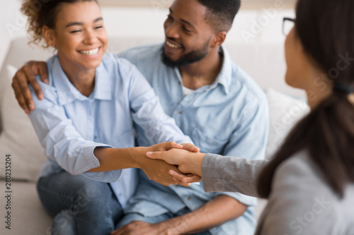 Cheerful african american spouses and psychologist handshaking in office