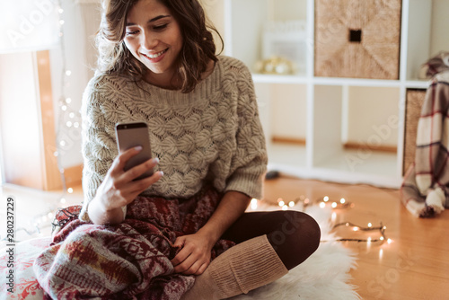 Obraz Woman texting in a smartphone - Christmas Season - fototapety do salonu
