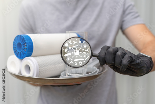 Vászonkép Service man hold water filtering cartridges with glass and spanner installation and magnifying glass with bacterium pollution impurity