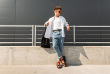 European Young Man Model In Stylish Clothes In Leather Red Sandals With A Black Bag In Sunglasses Is Resting Near The Metal Railing In The City. Handsome Hipster Guy. Fashionable Summer Menswear.
