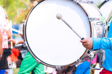 Drummer In Blue Uniforms A Marching Band. Drummer Plays Big Drum In Parade